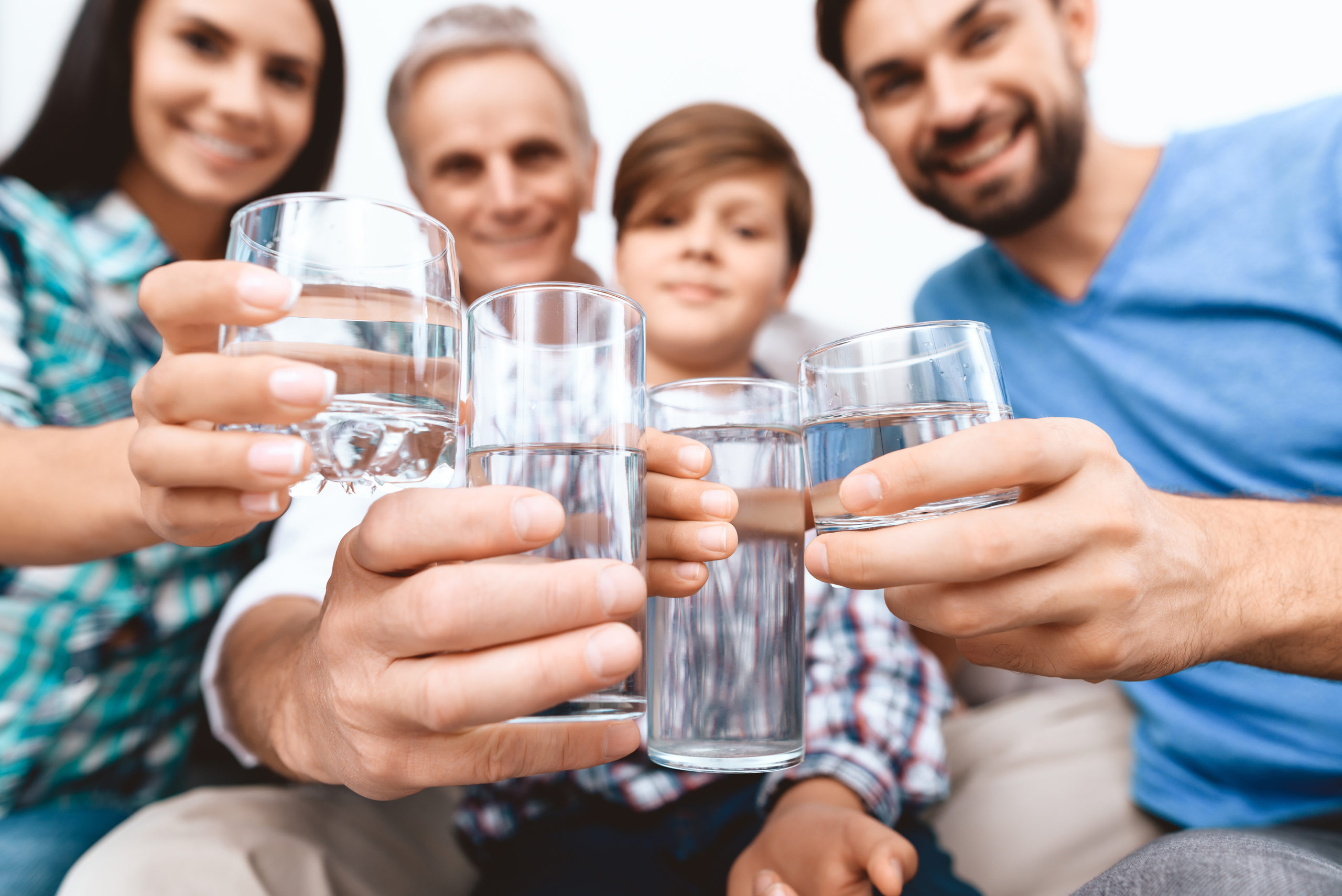 Close up. Cheerful Family cheering with glasses of water.